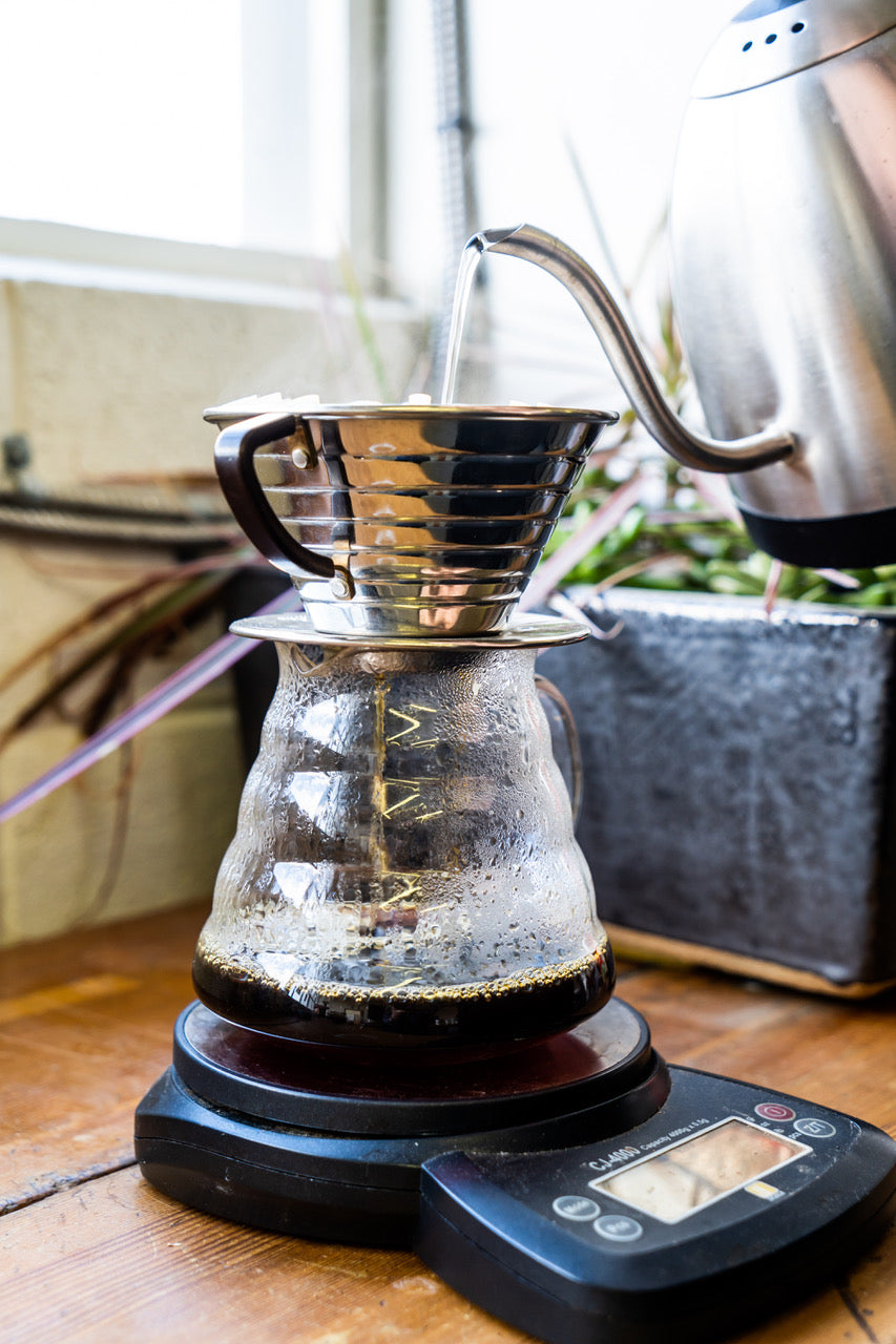 Brewing coffee in a kalita dripper on a scale with a gooseneck kettle