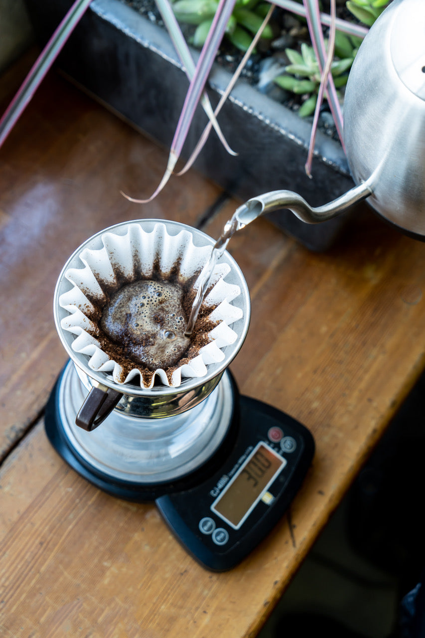 Birds eye view of a pour over being brewed in a kalita dripper with a gooseneck kettle