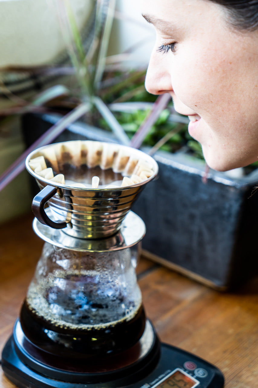 Woman enjoying the aroma of freshly brewed Kuma Coffee in a Kalita brewer