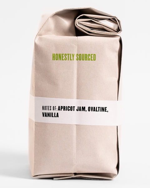 "The words ""honestly sourced"" printed in green on the side of a 12oz retail bag of Suke Quto, coffee roasted by Kuma Coffee, flavor notes of apricot jam, ovaltine and vanilla listed on the bottom third of the bag"