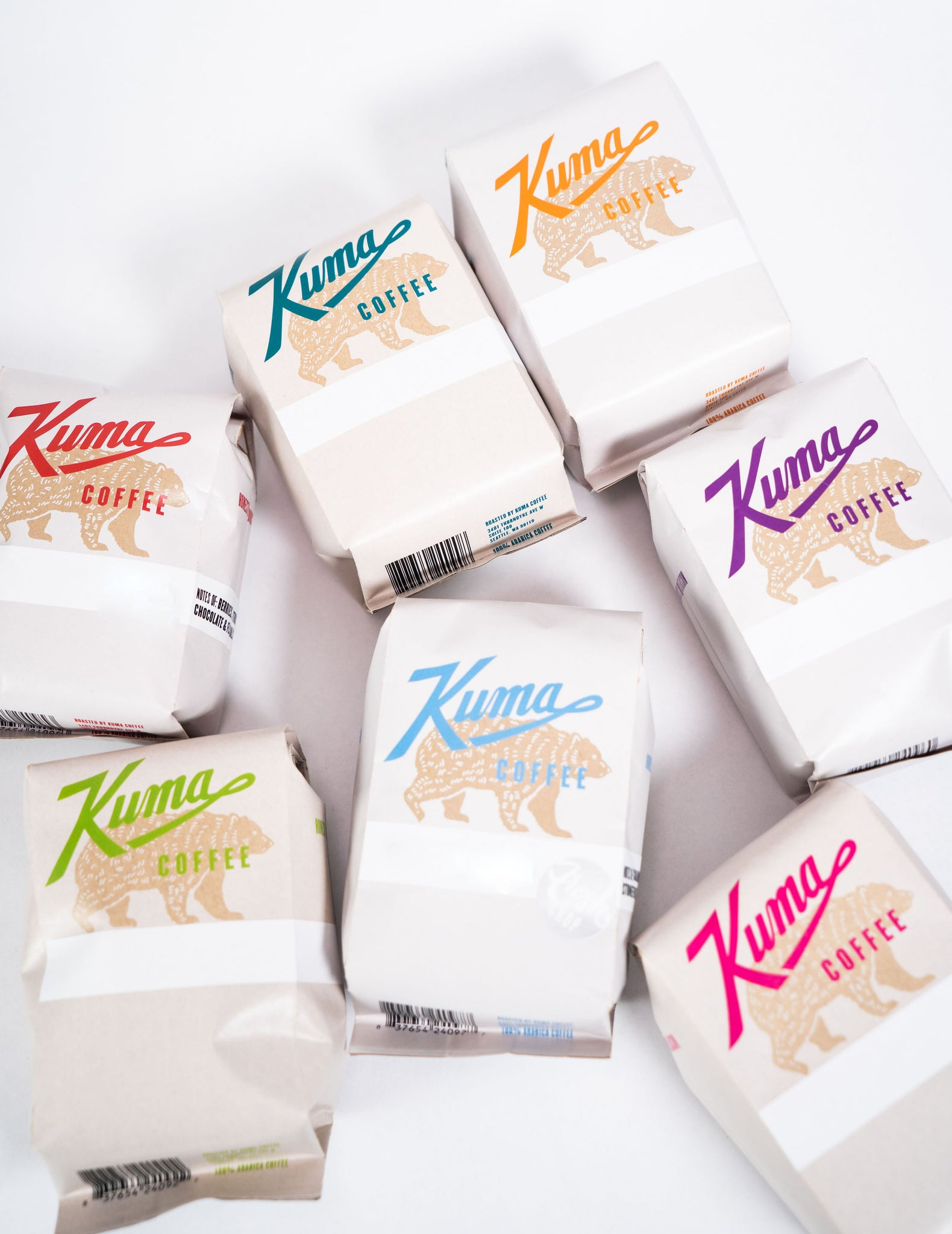 Seven 12oz bags of single origin Kuma Coffee, featuring a kraft brown bear with red, blue, teal, orange, purple, green and pink text