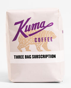 "A 12oz bag of Kuma Coffee, kraft brown bear with purple logo, the words ""three bag subscription"" written on the bottom third of the bag"