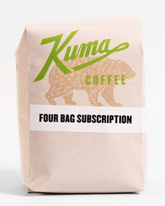 "A 12oz bag of Kuma Coffee, kraft brown bear with green logo, the words ""four bag subscription"" written on a white label on the middle of the bag"
