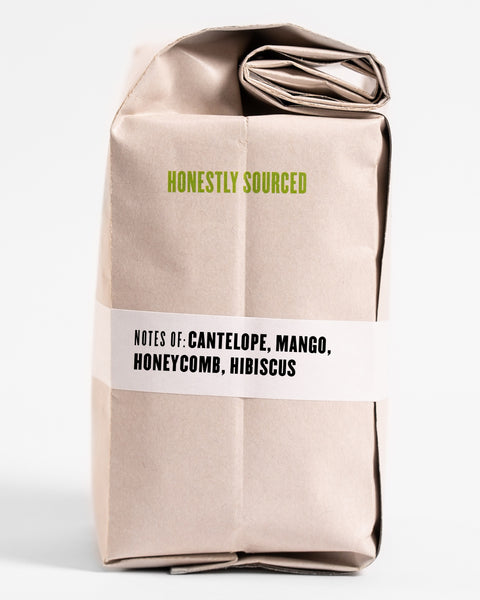 "The words ""honestly sourced"" printed in green on the side of a 12oz retail bag of Agaro Dera, coffee roasted by Kuma Coffee, flavor notes of cantelope, mango, honeycomb and hibiscus listed on the bottom third of the bag"