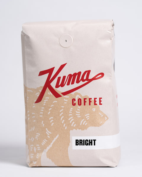 2.5lb bag of Kuma Coffee, kraft brown bear with red logo, the coffee name Bright written in the lower right corner