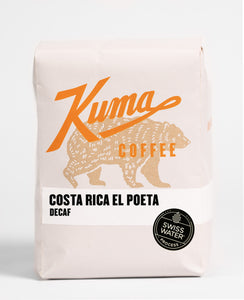 A 12oz bag of Kuma Coffee, kraft brown bear with orange logo, the name Costa Rica El Poeta, a decaf coffee with a Swiss Water Process sticker