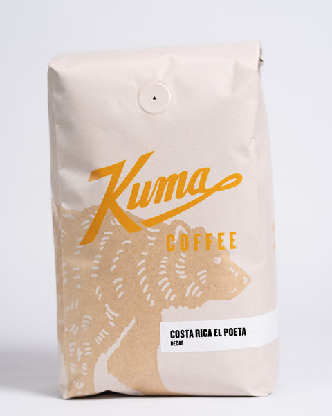 2.5 lb bag of Kuma Coffee, kraft brown bear with orange logo, the coffee name Costa Rica El Poeta, Decaf written in the lower right corner