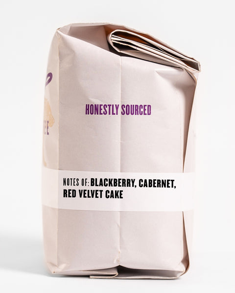 "The words ""honestly sourced"" printed in purple on the side of a 12oz retail bag of Gaikundo, coffee roasted by Kuma Coffee, flavor notes of blackberry, cabernet, and red velvet cake listed on the bottom third of the bag"