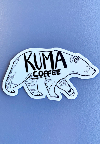 dye cut sticker of an illustration of a walking bear with the text kuma coffee written on it, blue background