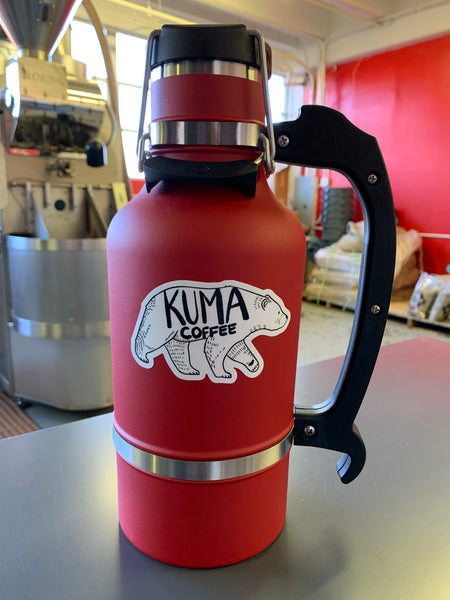 growler, on which a dye cut sticker of an illustration of a walking bear with the text kuma coffee written on it