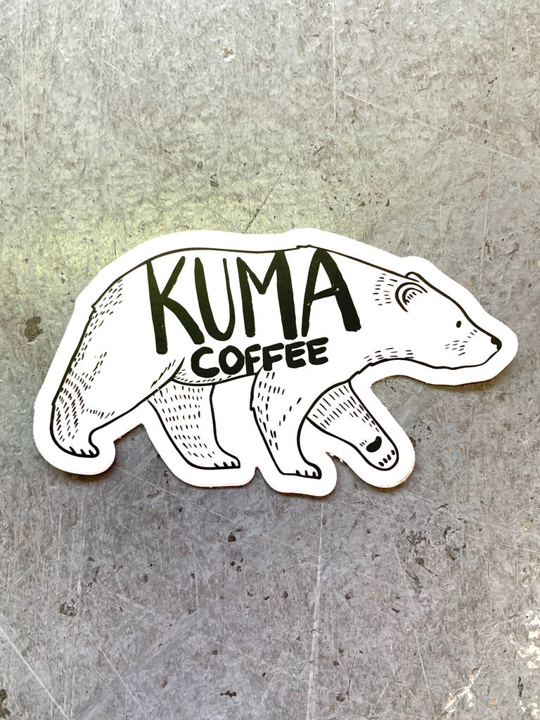 dye cut sticker of an illustration of a walking bear with the text kuma coffee written on it, concrete background