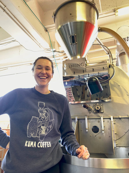woman smiling next to Loring Kestrel roaster at Kuma Coffee wearing sponge fleece crew neck sweatshirt by bella and canvas in heather navy, screen printed in Seattle Washington by Silkscreen co. with white bear roasting coffee with the text Kuma Coffee below