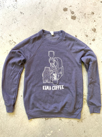 sponge fleece crew neck sweatshirt by bella and canvas in heather navy, screen printed in Seattle Washington by Silkscreen co. with white bear roasting on a Loring Kestrel with the text Kuma Coffee below