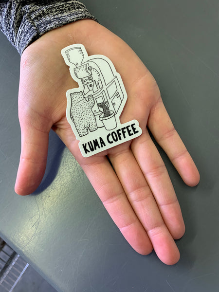 Hand holding a dye cut white sticker of illustration of bear roasting coffee on a Loring Kestrel with the text Kuma Coffee in black below