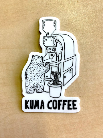 Dye cut white sticker of illustration of bear roasting coffee on a Loring Kestrel with the text Kuma Coffee in black below