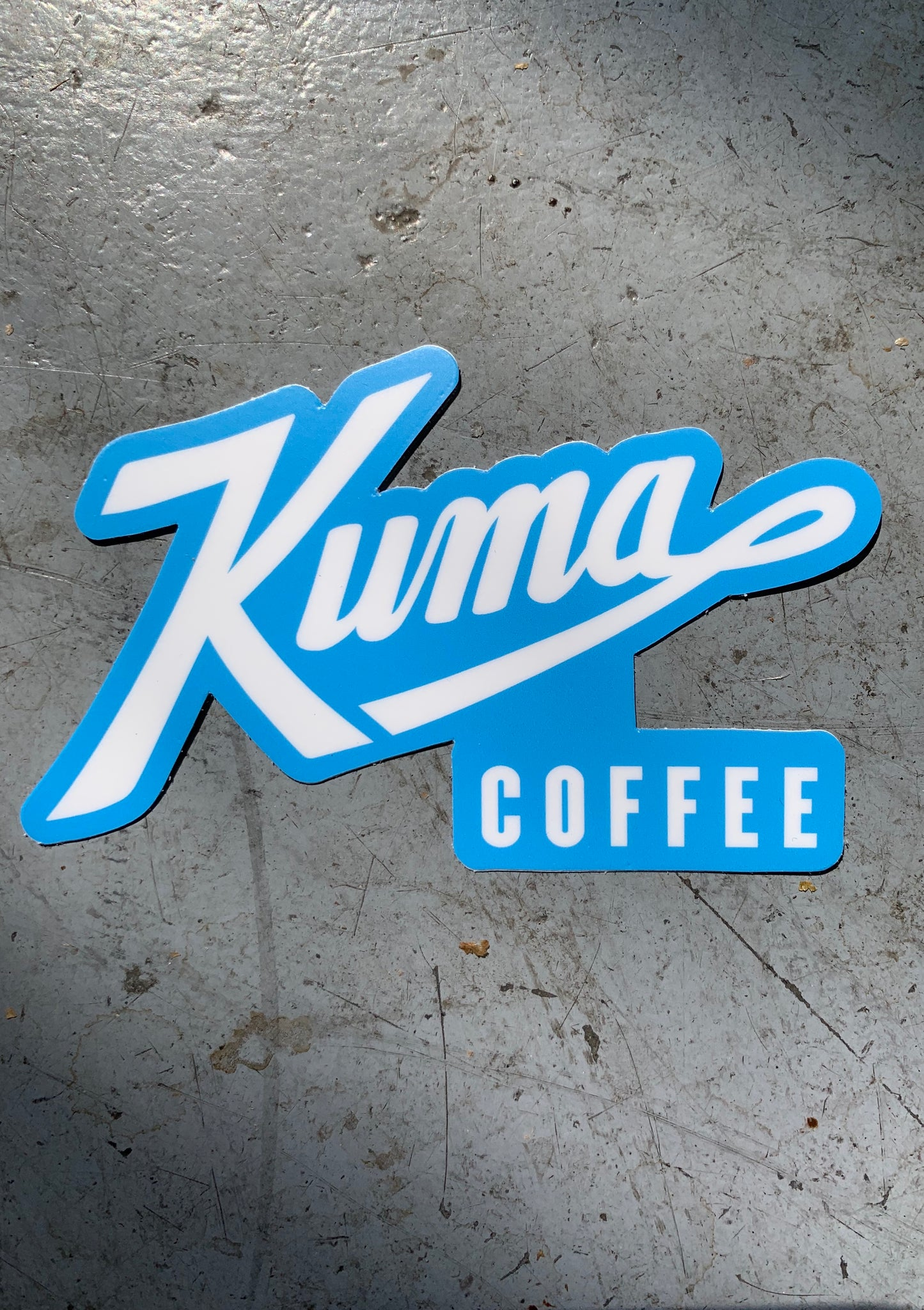 "A blue sticker with white text reading ""Kuma Coffee"""