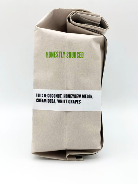 A kraft bag of coffee the text Notes of Coconut, Honeydew Melon, Cream Soda, White Grapes and stating Honestly Sourced