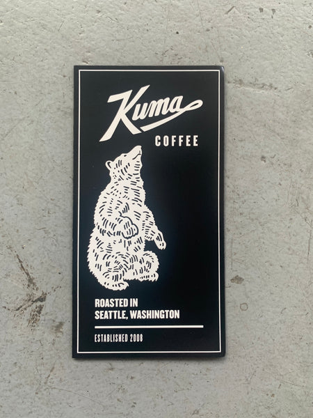 "A rectangular, black magnet that features a white bear sitting on its hind legs. The words Kuma Coffee printed on the top third in white text. The words ""Roasted in Seattle, Washington, Established 2008"" written on the bottom third"