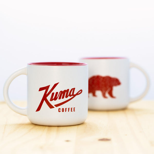 14 oz stoneware coffee mug with white exterior, Kuma Coffee logo in red on one side and bear logo in red on other side, red interior