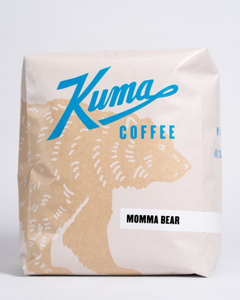 5lb bag of Kuma Coffee, kraft brown bear with blue logo, the coffee name Momma Bear written in the lower right corner