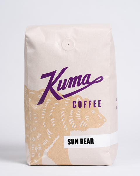 2.5 lb bag of Kuma Coffee, kraft brown bear with purple logo, the coffee name Sun Bear written in the lower right corner