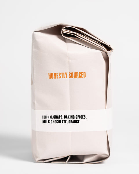 "The words ""honestly sourced"" printed in orange on the side of a 12oz retail bag of Momma Bear, coffee roasted by Kuma Coffee, flavor notes of grape, baking spices, milk chocolate and orange, listed on the bottom third of the bag"