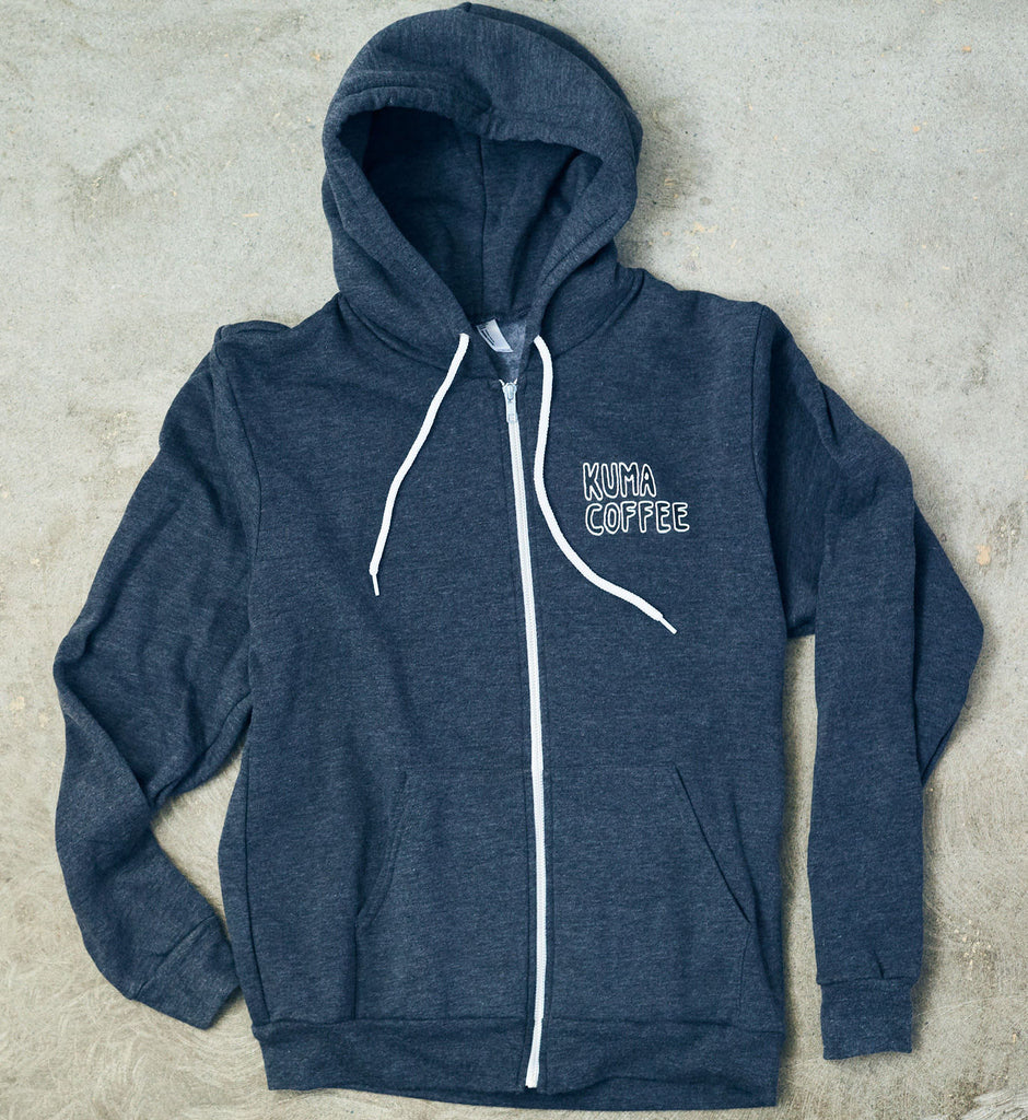 Heather grey front of zip up hoodie, white strings and zipper, with illustrated text Kuma Coffee on front left breast