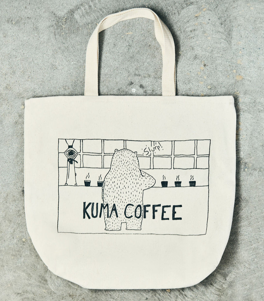 Front of a cream colored tote bag, with an illustration of a bear cupping coffee at a bar in front of windows, with the drawn text kuma coffee beneath
