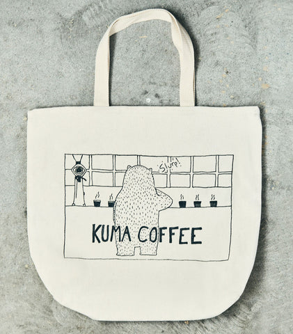 10 ounce cream colored tote made from 100% cotton twill with the image of a bear cupping coffee and Kuma Coffee written below