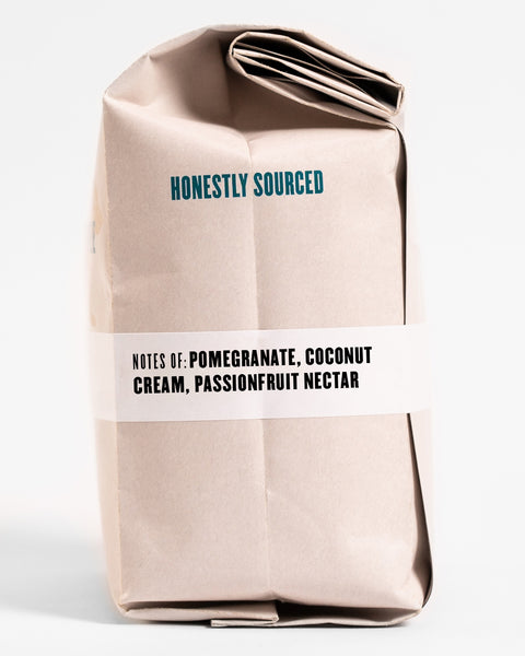 "The words ""honestly sourced"" printed in teal on the side of a 12oz retail bag of Maria Elsi, coffee roasted by Kuma Coffee, flavor notes of pomegranate, coconut cream and passionfruit nectar listed on the bottom third of the bag"