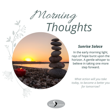 Sunrise with rocks piled on top of each other and a candle.