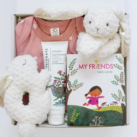 KADOO Baby girl gift box wrapped in Furoshiki pink polka dots cotton. Contains pink polka dots onesie from Organic Cotton, Taro Gomi's My Friends board book, Mary Meyer's bunny rattle and bunny lovey, and Vivaiodays organic wash and shampoo.