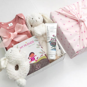 KADOO Baby shower gift box wrapped in Furoshiki pink polka dots cotton. Contains pink polka dots onesie from Organic Cotton, Taro Gomi's My Friends board book, Mary Meyer's bunny rattle and bunny lovey, and Vivaiodays organic wash and shampoo.