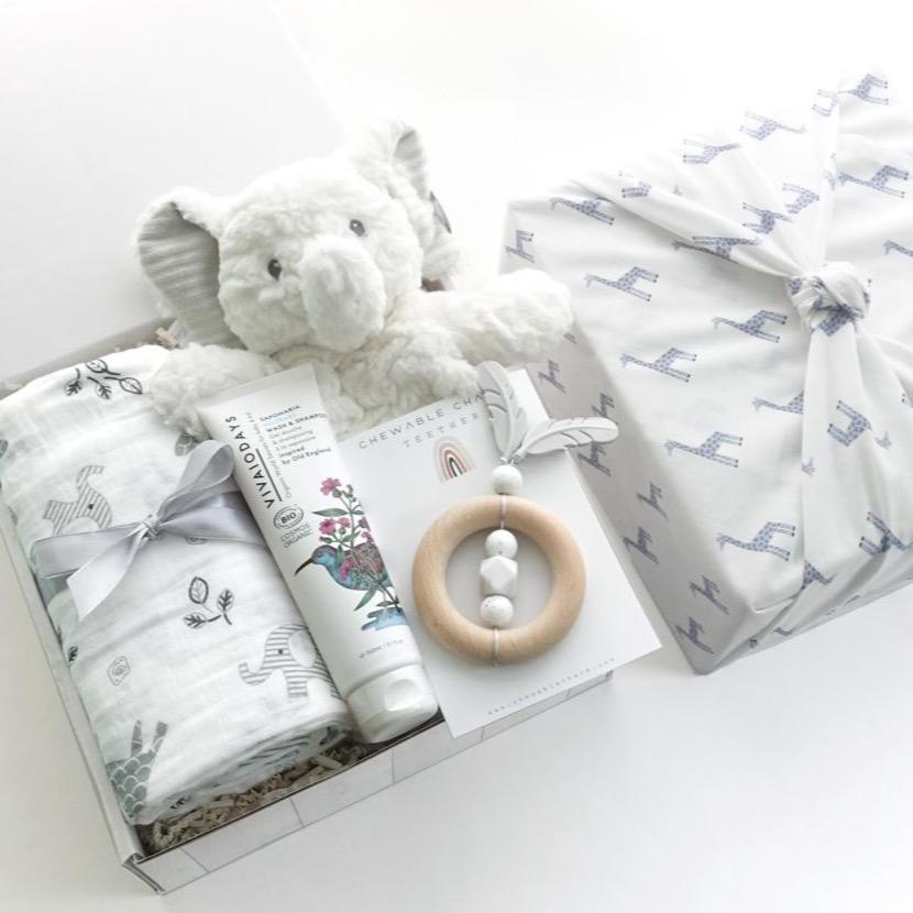 KADOO gender neutral baby gift box wrapped in Furoshiki giraffe pattern cotton. Contains Mary Meyer Elephant lovey, Lulujo Afrique Cotton Muslin Swaddle, Chewable Charm silicon wooden teether, and Vivaiodays natural body wash and shampoo.
