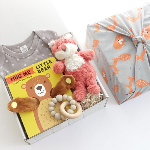 KADOO gender neutral gift box wrapped in Furoshiki Fox pattern cotton. Contains grey dots or brown dots onesie from Colored Organic, Chronicle Books Hug me Little Bear Finger Puppet book, Mary Meyer's Fox stuffed animals, and a handmade BPA Free Silicon + wooden rattle.