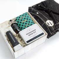 KADOO Dapper Man gift box with galaxy space special edition cotton bandana in black solar system pattern Father's Day or Gift for him. Content Goodio Mint Chocolate, Men's Society Weekender Wash Kit, Handsome Shave cream, Nawrap organic Face Towel Wilder & Co hand sanitizer.
