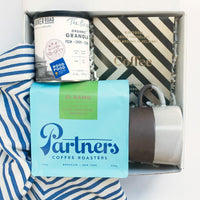 KADOO Coffee Society gift box. Contains Partner's Coffee BRoasters, Goodio Espresso chocolate bar, Banner Road Baking Granola, a brown and white mug, and Hemlock Goods Stripes Bandana.