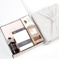 KADOO The Desk Essential gift box. Wrapped in Furoshiki linen fabric. Content: journal, desk notepad, ginger cookie, hand sanitizer & caramel candies