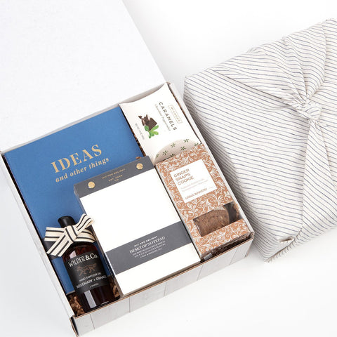 KADOO The Desk Essential – Back at work gift box. Wrapped in 100% stripes French linen in Furoshiki style. Content: journal, desk notepad, ginger snap cookie, hand-sanitizer and caramel candies.