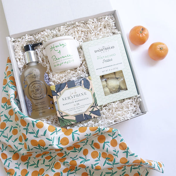 KADOO Welcome Home Gift Box wrapped in Furoshiki style with Lemon or Tangerine Cotton fabric, and a choice of dry flowers bouquet. Featuring lavender scented hand wash, a beautiful ceramic candle, a jar of Herbs de Provence spices and homemade pistachio shortbreads.