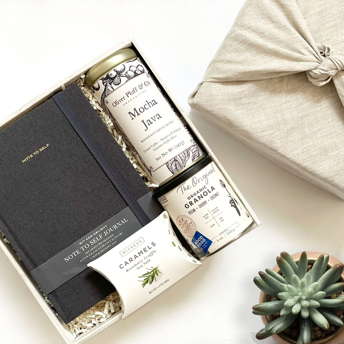 KADOO The Home Office – Desk essential gift box wrapped in Furoshiki linen. Wit & delight journal in black, McCrea's sea salt truffle caramel, Oliver Pluff & Co Mocha Java, Banner Road Granola. Unique and creative corporate gifts.