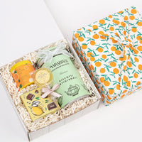 KADOO lemon twist gift box for the holiday. Wrapped in sustainable 100% cotton - Orange Tangerine print, in Furoshiki style. Featuring: Orange black tea, dark chocolate covered lemon candy, lemon honey lollipop and Italian butter cookies.