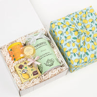 KADOO lemon twist gift box for the holiday. Wrapped in sustainable 100% cotton - Lemon print, in Furoshiki style. Featuring: Orange black tea, dark chocolate covered lemon candy, lemon honey lollipop and Italian butter cookies.