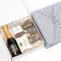 KADOO The Cheers gift box wrapped in Furoshiki style with blue French linen. For graduation, celebration and special occasion. Contains Zero Blanc sparkling wine, dark chocolate, rosemary truffle almonds and Rosemary Truffle Sea Salt caramels.