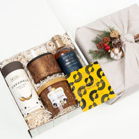 KADOO Holiday Treats gift box. Perfect gift for men. Wrapped in 100% French linen in Furoshiki style. Contains: caramel candies, whiskey glass, popcorn, maple cinnamon syrup & licorice dark chocolate.