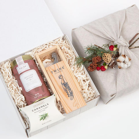 KADOO The Vineyards, gift box for wine love. Featuring: a mulling spice blend, rosemary truffle sea salt caramels; a keepsake corkscrew in a wooden box; wrapped in reusable 100% French linen with a choice of holiday bouquet.