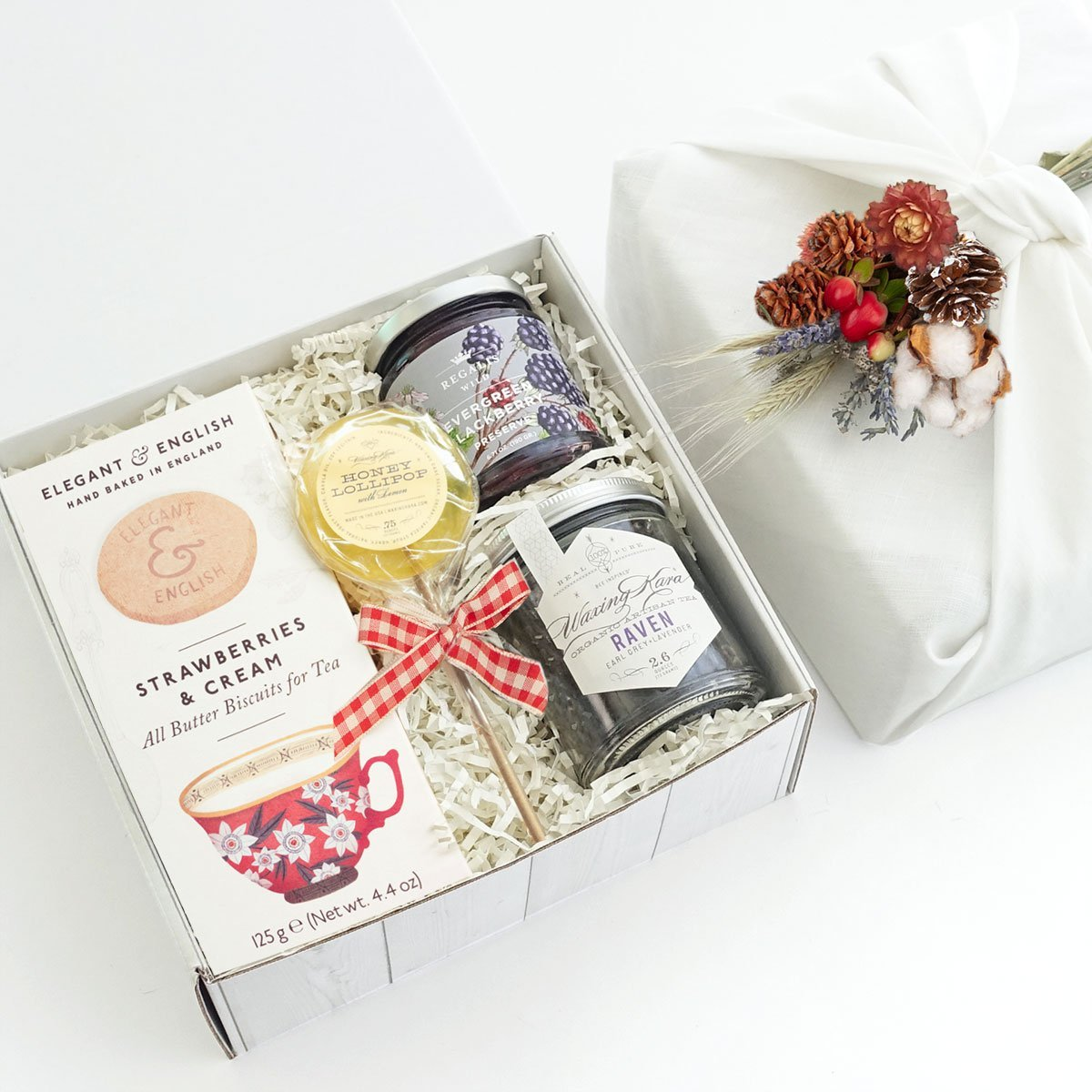 KADOO Thinking of You Care Package Gift Box wrapped in Furoshiki style with white French linen and bouquet of dry flowers. Featuring Strawberries Cream cookies, Evergreen Blackberry Jam, Earl Grey Tea and Honey Lollipops.