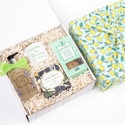 KADOO Cozy Home Gift Box wrapped in Furoshiki style with Lemon or Tangerine Cotton fabric, and a choice of dry flowers bouquet. Featuring lavender hand wash, ceramic candle, a jar of Herbs de Provence spices and homemade brown butter cookies.