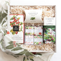 KADOO The Mistletoe Holiday gift box. Contains: Amedei Dark chocolate Bar, McCrea's Rosemary Truffle Sea Salt caramels, Via Mercato Natale Shea butter soaps, and Frosted Forest room diffuser. Wrapped in organic kitchen towel in berry pattern.
