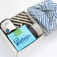 KADOO Coffee Society gift box. Contains Partner's Coffee , Goodio Espresso chocolate bar, Banner Road Baking Granola, a brown and white mug, and Hemlock Goods Stripes Bandana.